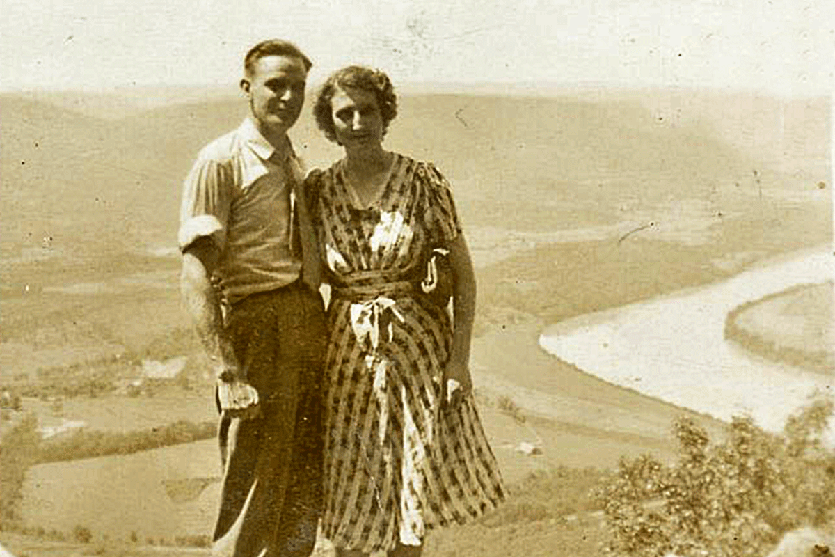 Couple posing on mountaintop overlooking a river valley.