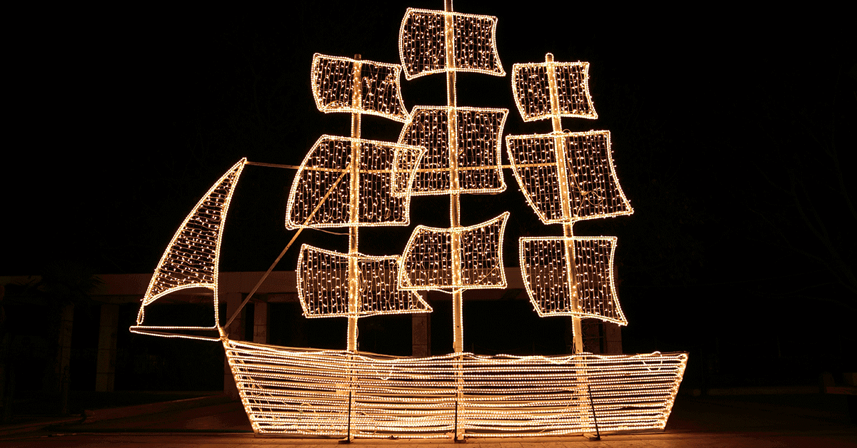 Small wooden ship with string lights attached.
